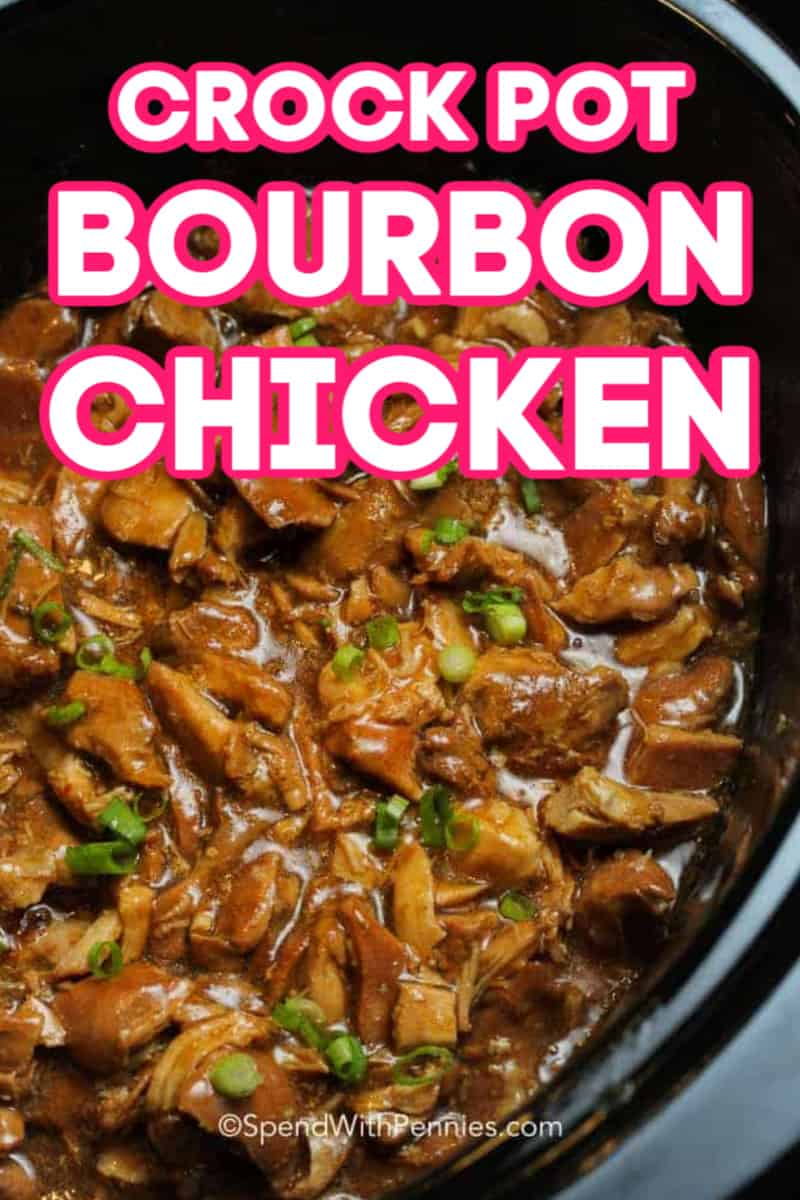 A Crock Pot full of bourbon chicken topped with green onions.