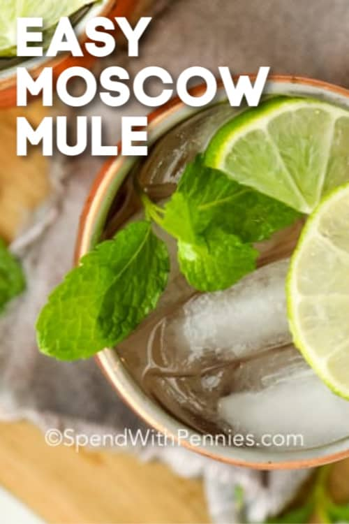 A Moscow Mule cocktail garnished with lime wedges and mint leaves with writing.