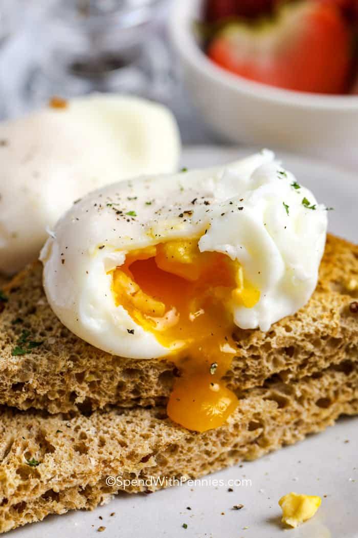 a poached egg broken open over toast