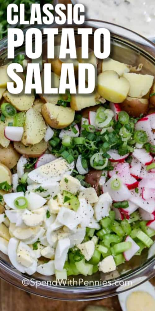 Ingredients to make Potato Salad assembled in a glass bowl with writing.