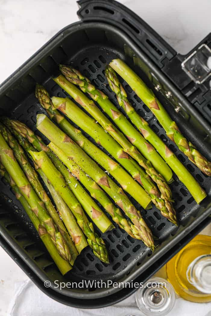 Fresh asparagus and seasonings in an air fryer basket