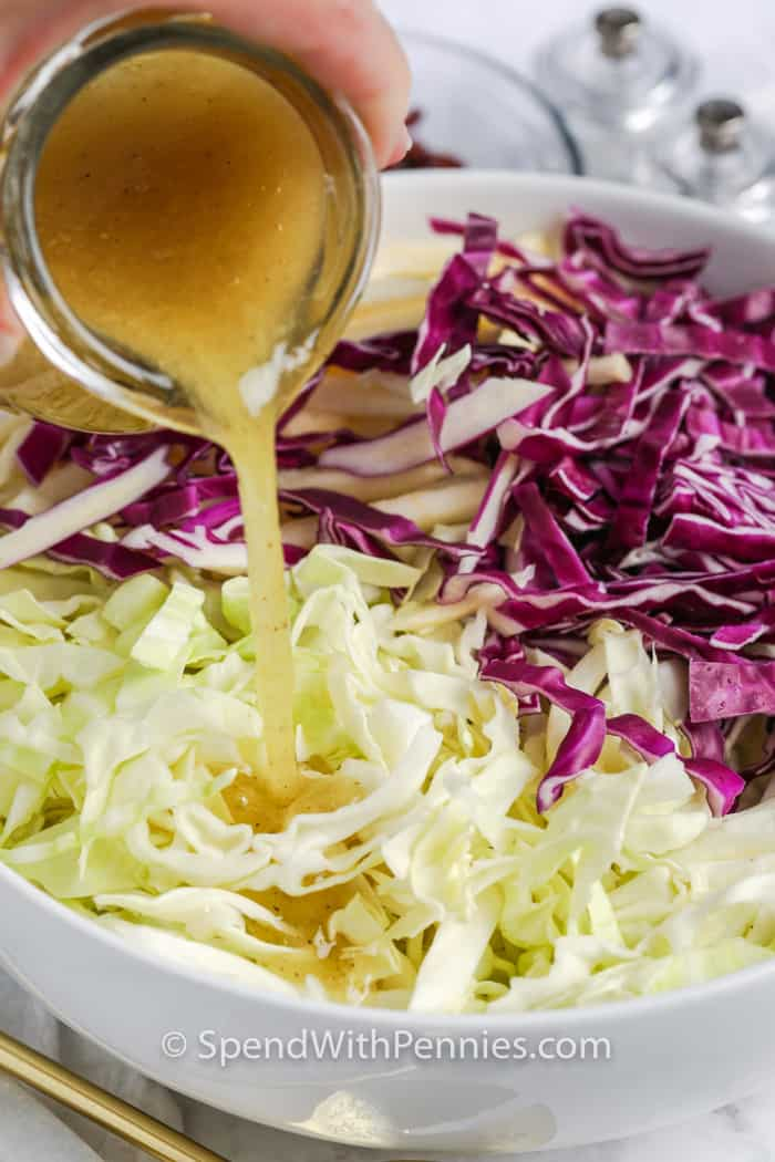 salad dressing being poured over Cabbage Salad