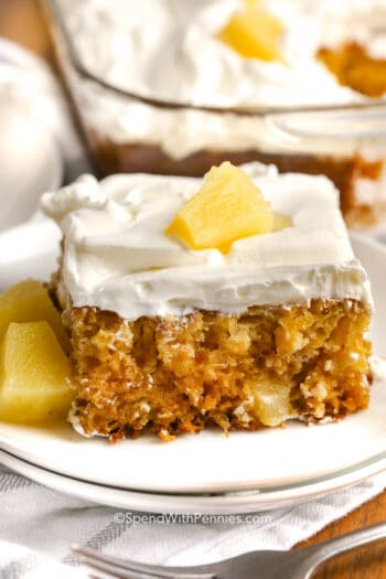 A slice of pineapple cake topped with pineapple and whipped topping