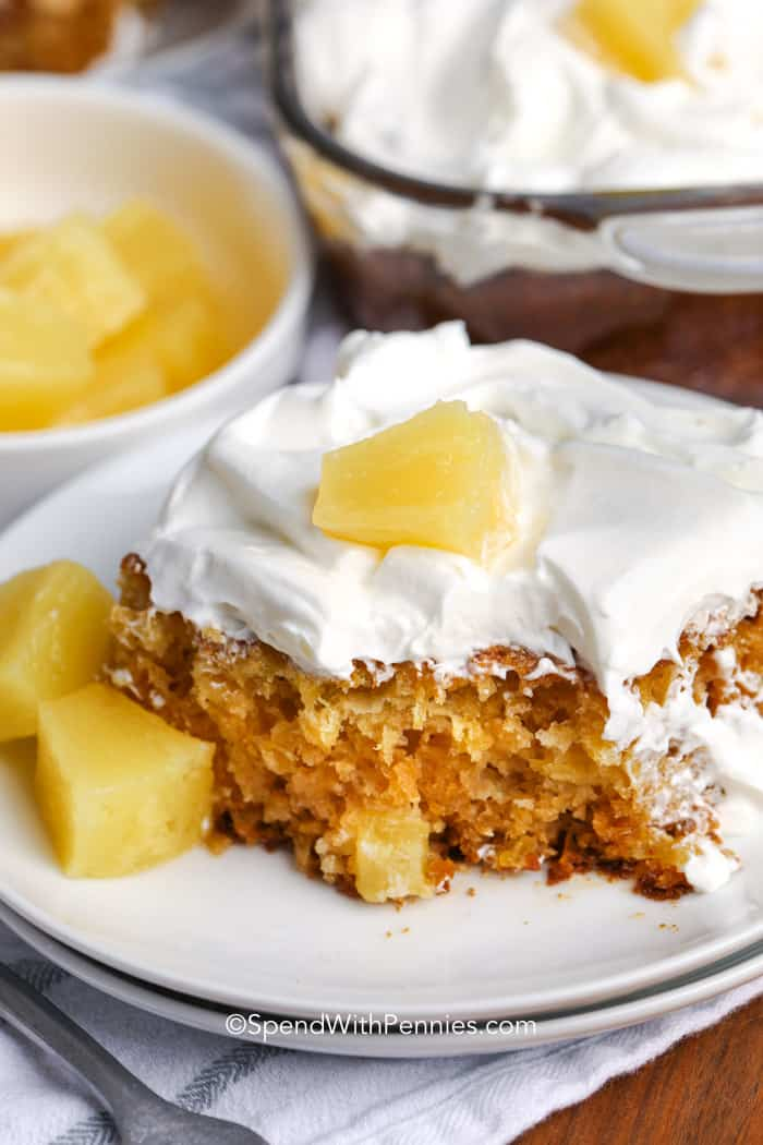 A slice of pineapple cake on a white plate topped with whipped topping