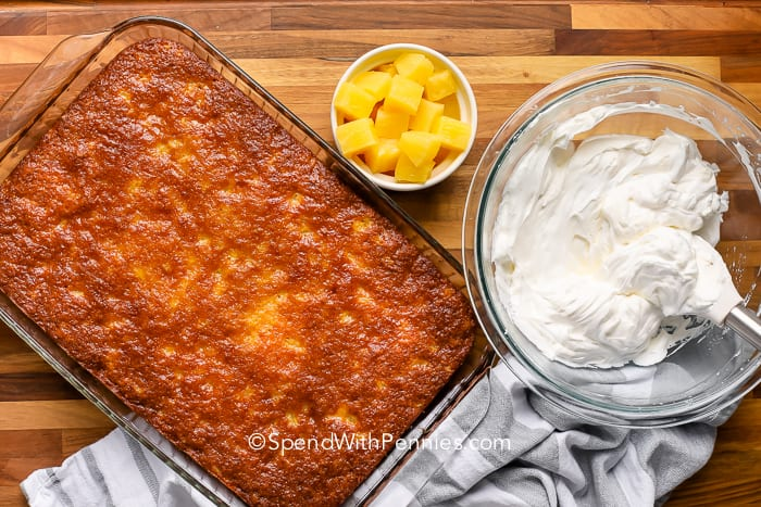 Baked pineapple cake with pineapple and topping beside it.