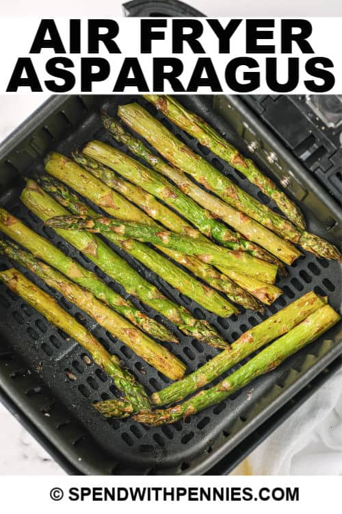 Asparagus in an air fryer basket with writing