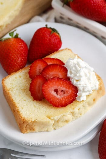 Slice of pound cake on a white plate with whipped cream and strawberries on top with strawberries on the side