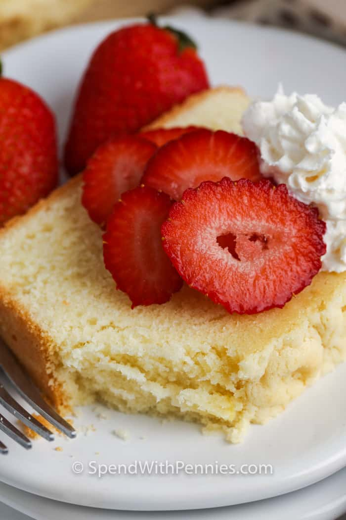 Slice of pound cake on a white plate with strawberries and whipped cream with a bite taken out of the pound cake