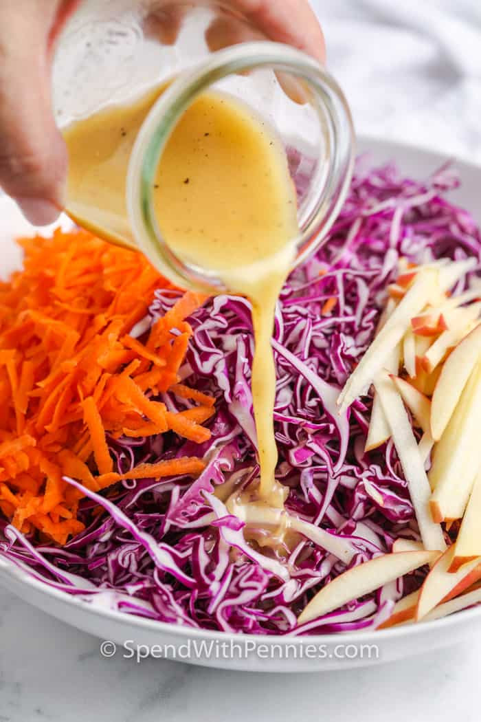 dressing being poured over red cabbage slaw ingredients