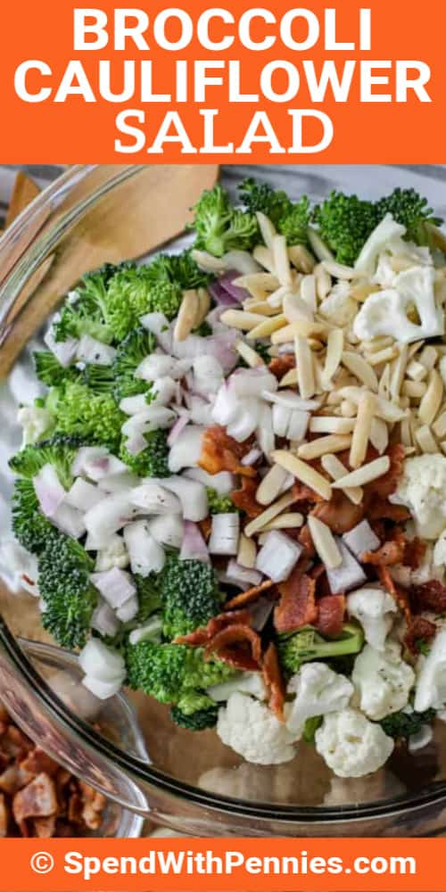 Broccoli Cauliflower Salad ingredients in a clear mixing bowl with dressing and bacon next to it, with a title.