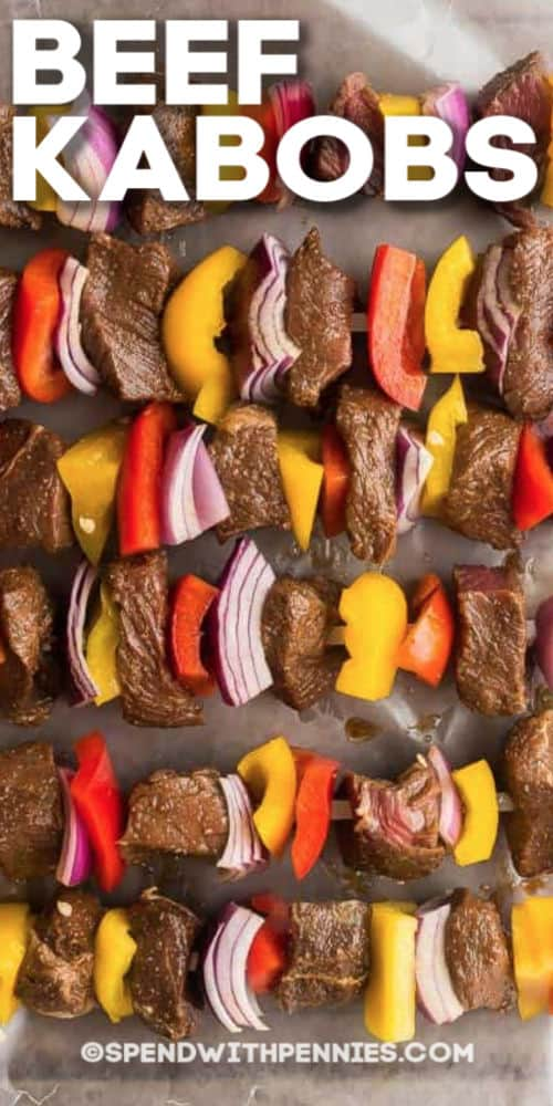 Beef kabobs on a baking tray with writing