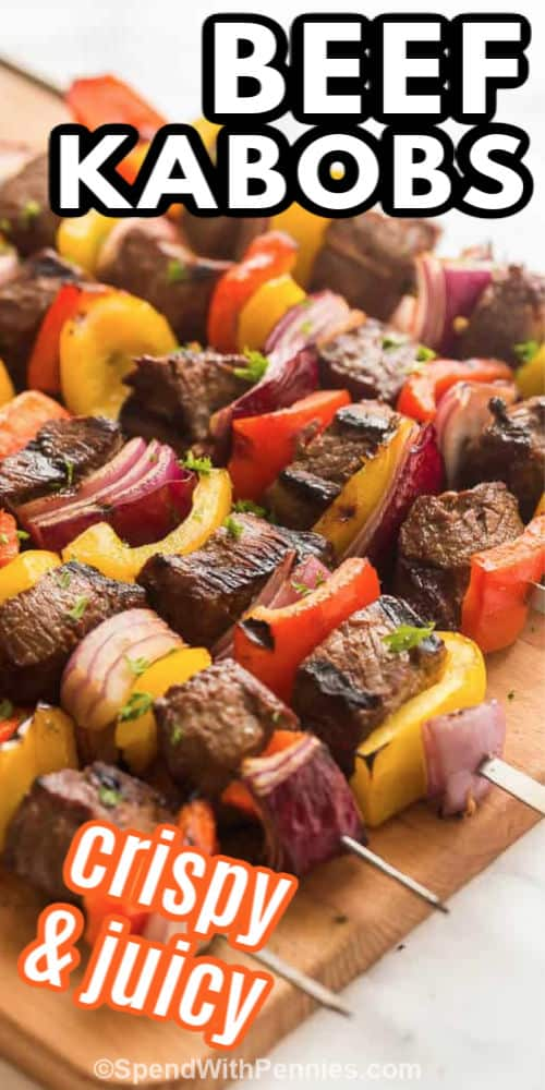 Beef kabobs on a cutting board with writing