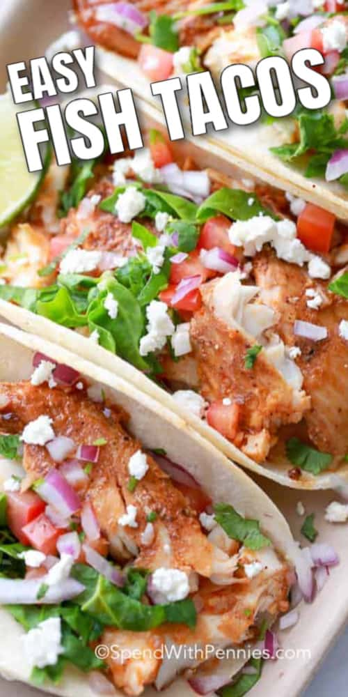 Fish Tacos lined up in a tray with toppings and lime wedges, with writing