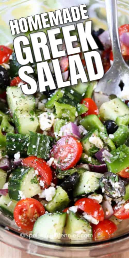 Greek Salad in a clear mixing bowl with writing