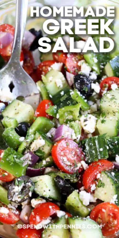 Homemade Greek Salad in a clear bowl with a spoon and a title