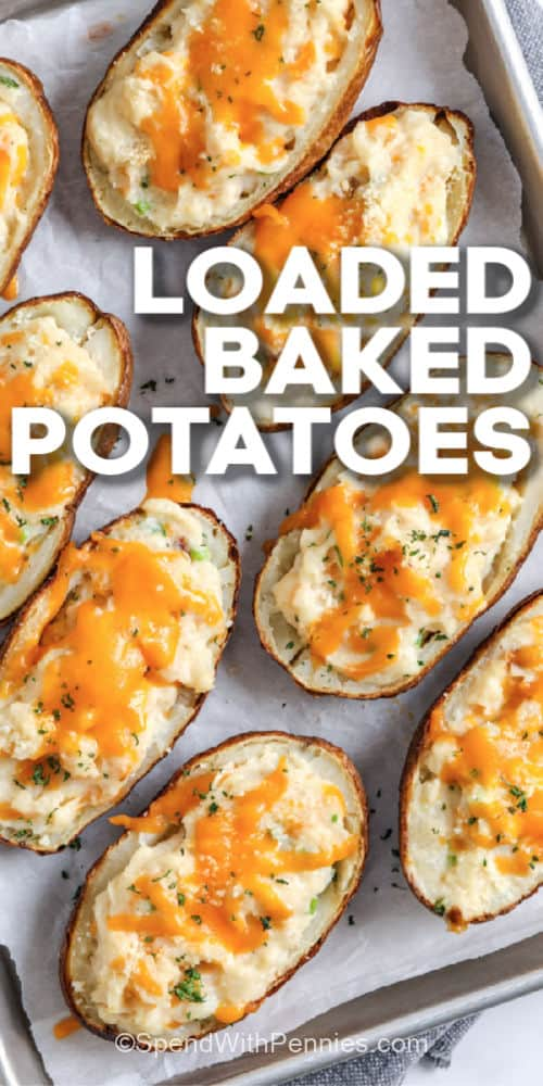 Loaded Baked Potatoes on a baking sheet with writing