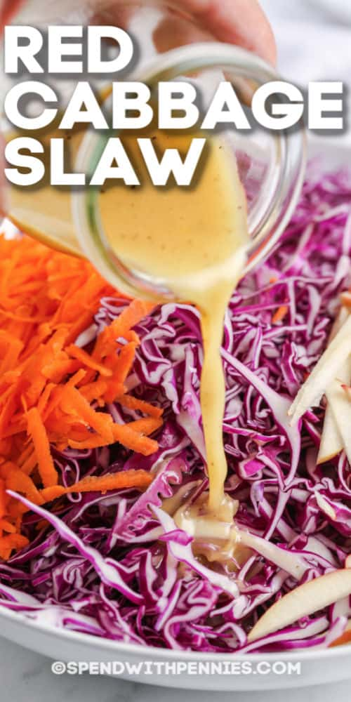 dressing being poured over red cabbage slaw with writing