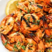 Sriracha Grilled Shrimp on a white plate with lemon slices