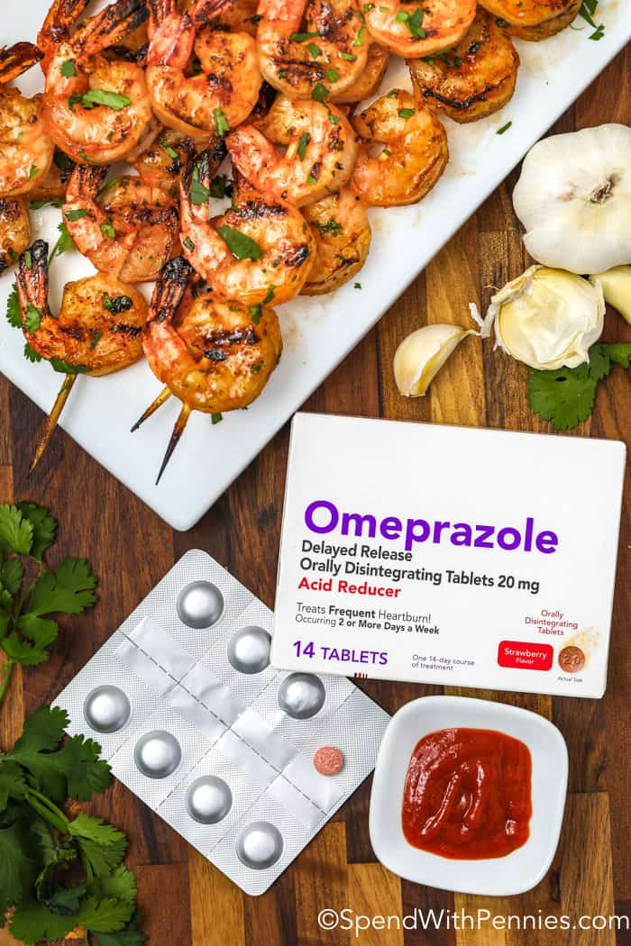 Overhead shot of cooked shrimp on skewers and a package of Omeprazole