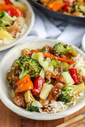Pork Stir Fry in a white bowl with frying pan and bowl of the dish behind it