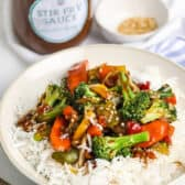 Stir Fry Sauce on top of rice and vegetables in a white bowl with chop sticks beside