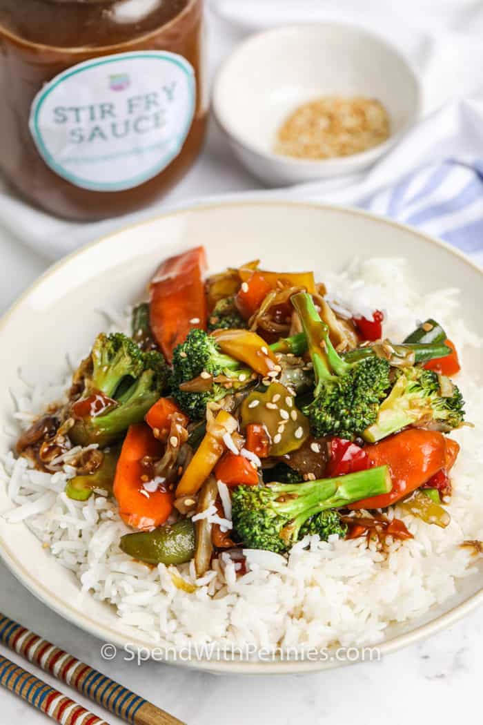 Stir Fry Sauce over rice and vegetables with jar in the background