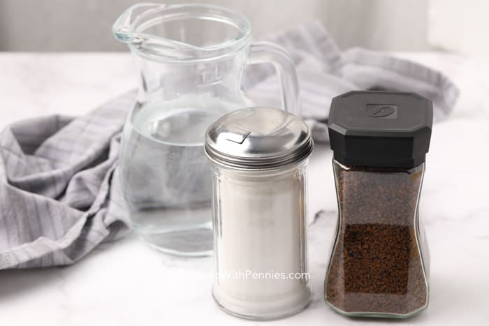 Ingredients for making whipped coffee with water in the background