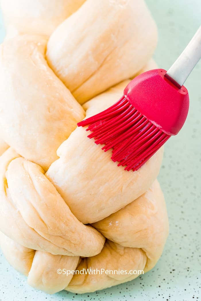 A pastry brush brushing egg wash on Challah bread.