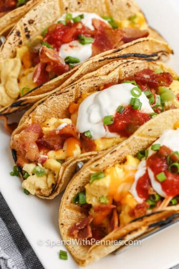 3 breakfast tacos folded with sour cream and salsa on top