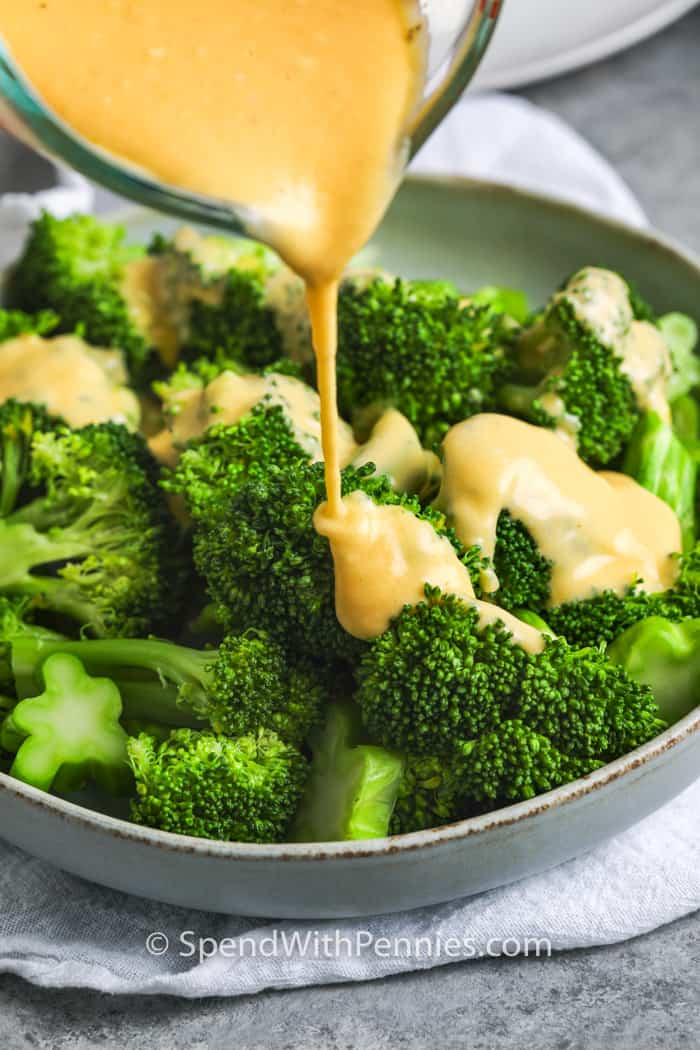 cheese being poured over broccoli to make Broccoli with Cheese