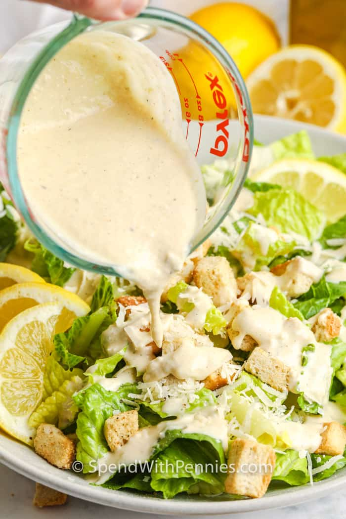 pouring dressing on Caesar Salad with lemons behind