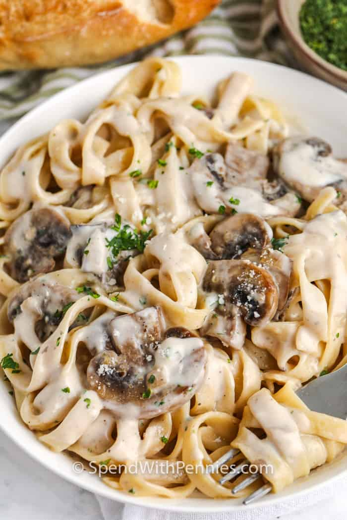 Creamy Mushroom Tagliatelle in a white bowl with bread behind