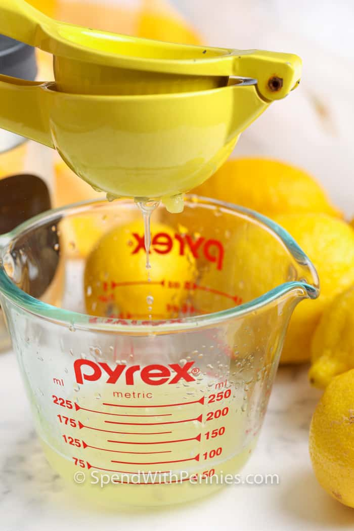 lemon being squeezed into a measuring cup to make Homemade Lemonade