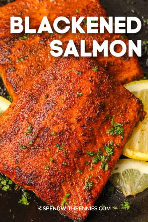 two pieces blackened salmon with parsley and lemon slices with writing