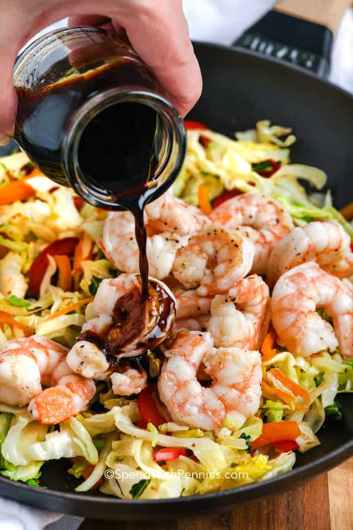 pouring sauce over shrimp and vegetables to make lo mein