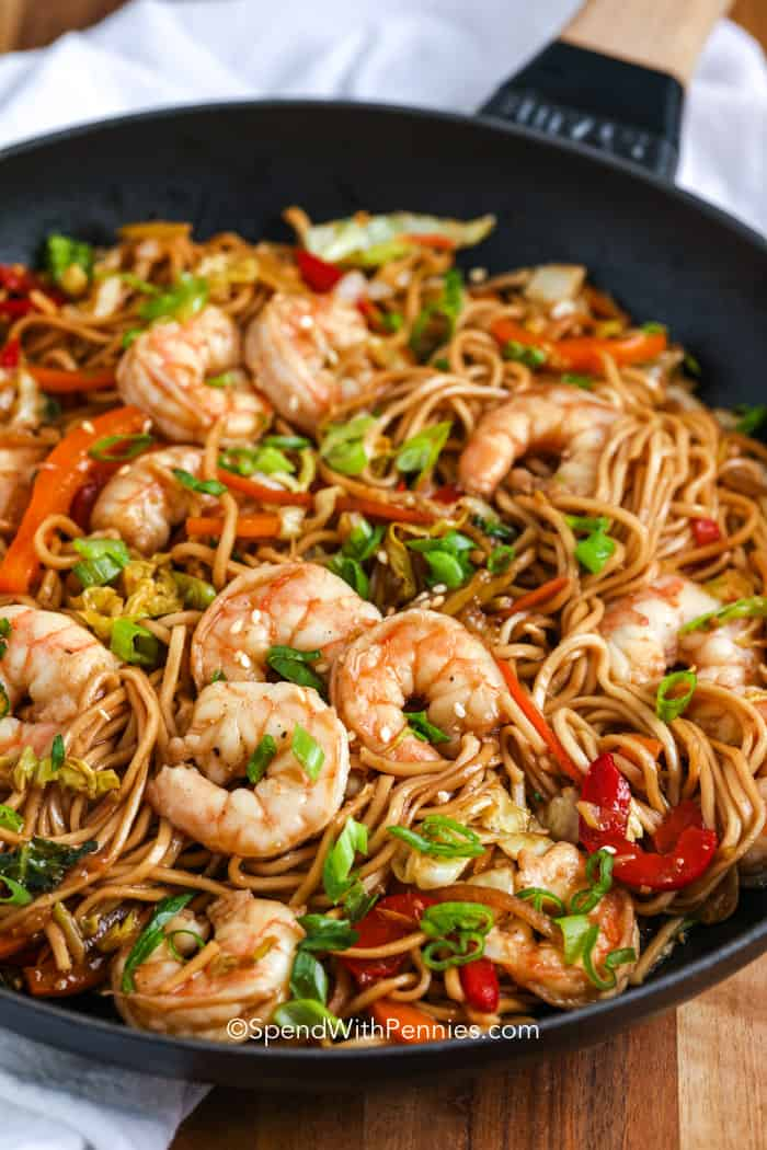 A pan of shrimp lo mein garnished with green onions on a wood cutting board