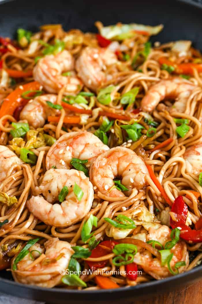 A close up image of shrimp lo mein with vegetables in a pan