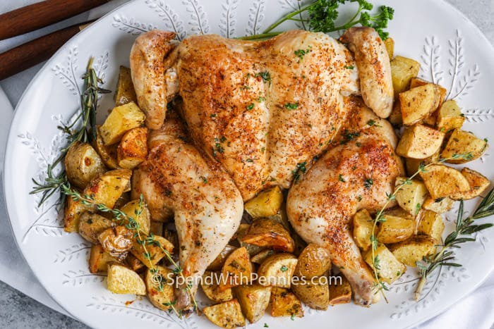Spatchcock Chicken on a white platter with potatoes