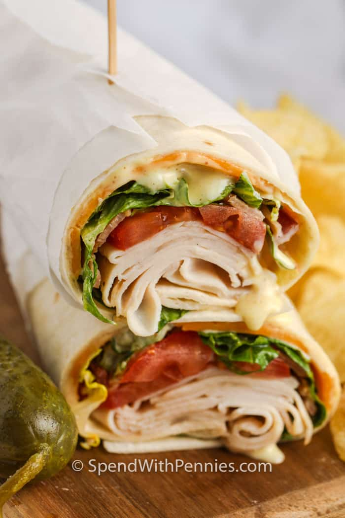 Turkey Wrap close up on a cutting board with chips and a pickle