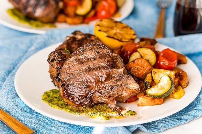 lamb chops on a white plate with veggies.