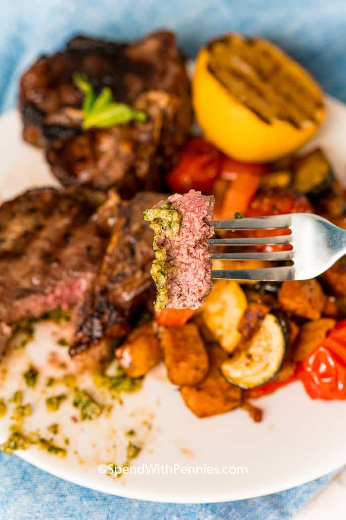 A fork holding up a bite of lamb chop.