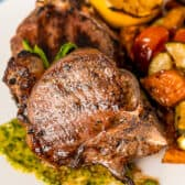 Grilled lamb chops plates with veggies on a white plate.