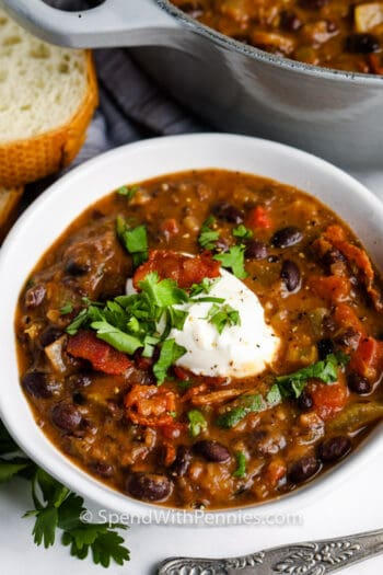 Black Bean Soup in a bowl with a pot and bread in the background