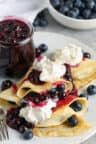 Blueberry Crepes on a white plate with whipped cream and blueberries surrounding it