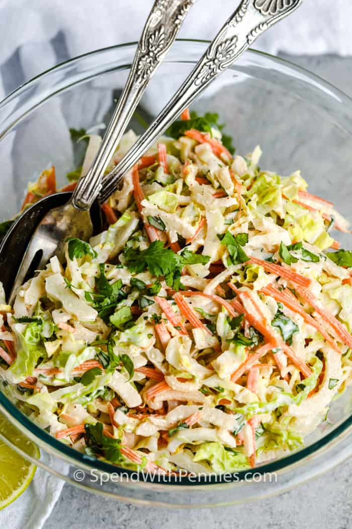 Cilantro Lime Coleslaw in a glass bowl with spoons