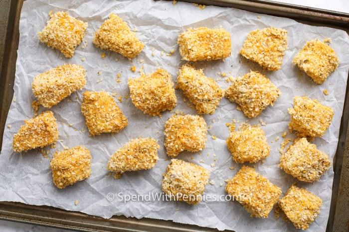 Fish nuggets on a baking sheet before baking