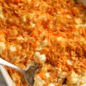 Funeral Potatoes in a casserole dish with a spoon