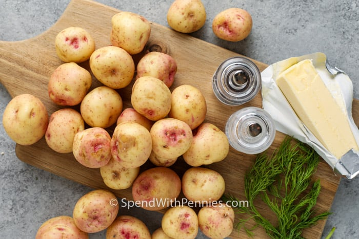 ingredients to make Garlic Dill New Potatoes on a wooden cutting board