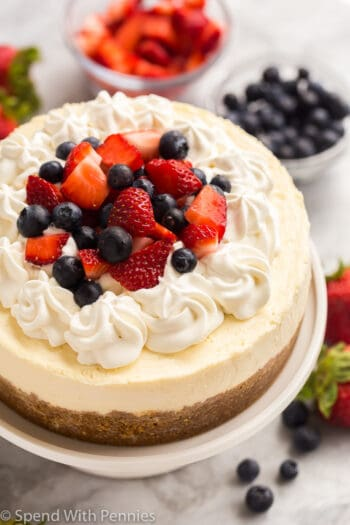 instant pot cheesecake on white cake plate with whipped cream and berries