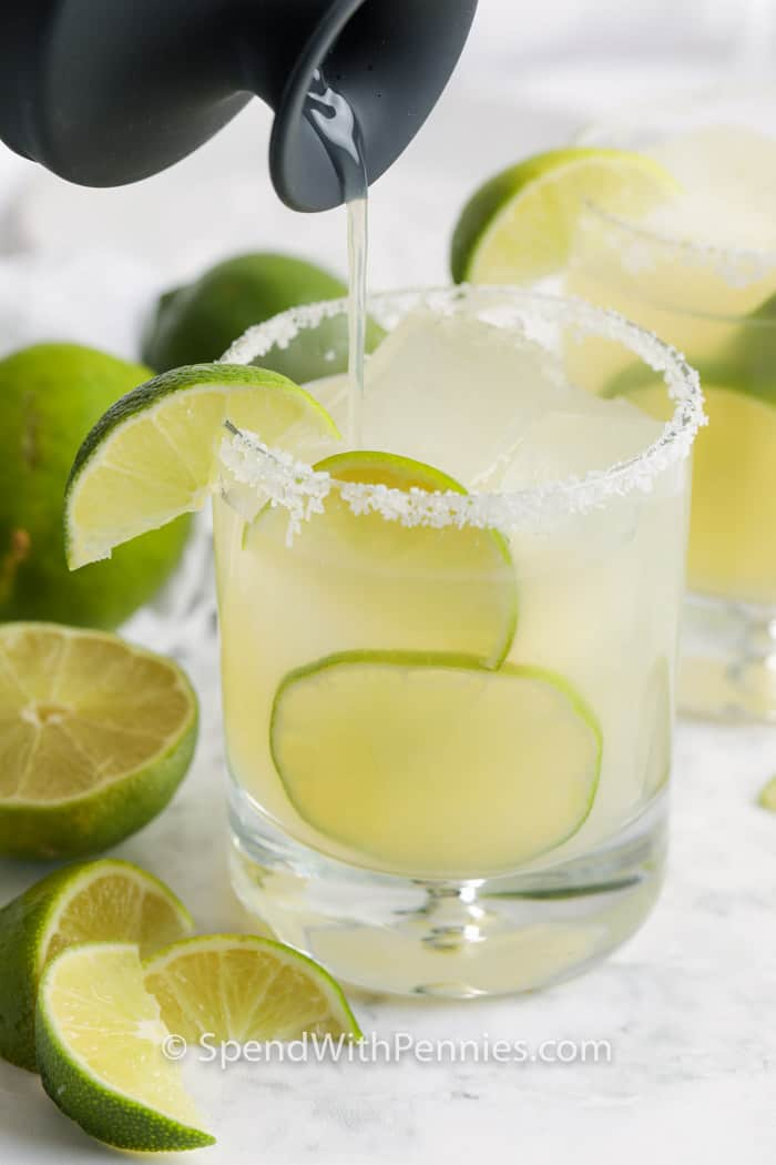 pouring Margarita in a glass of limes and ice